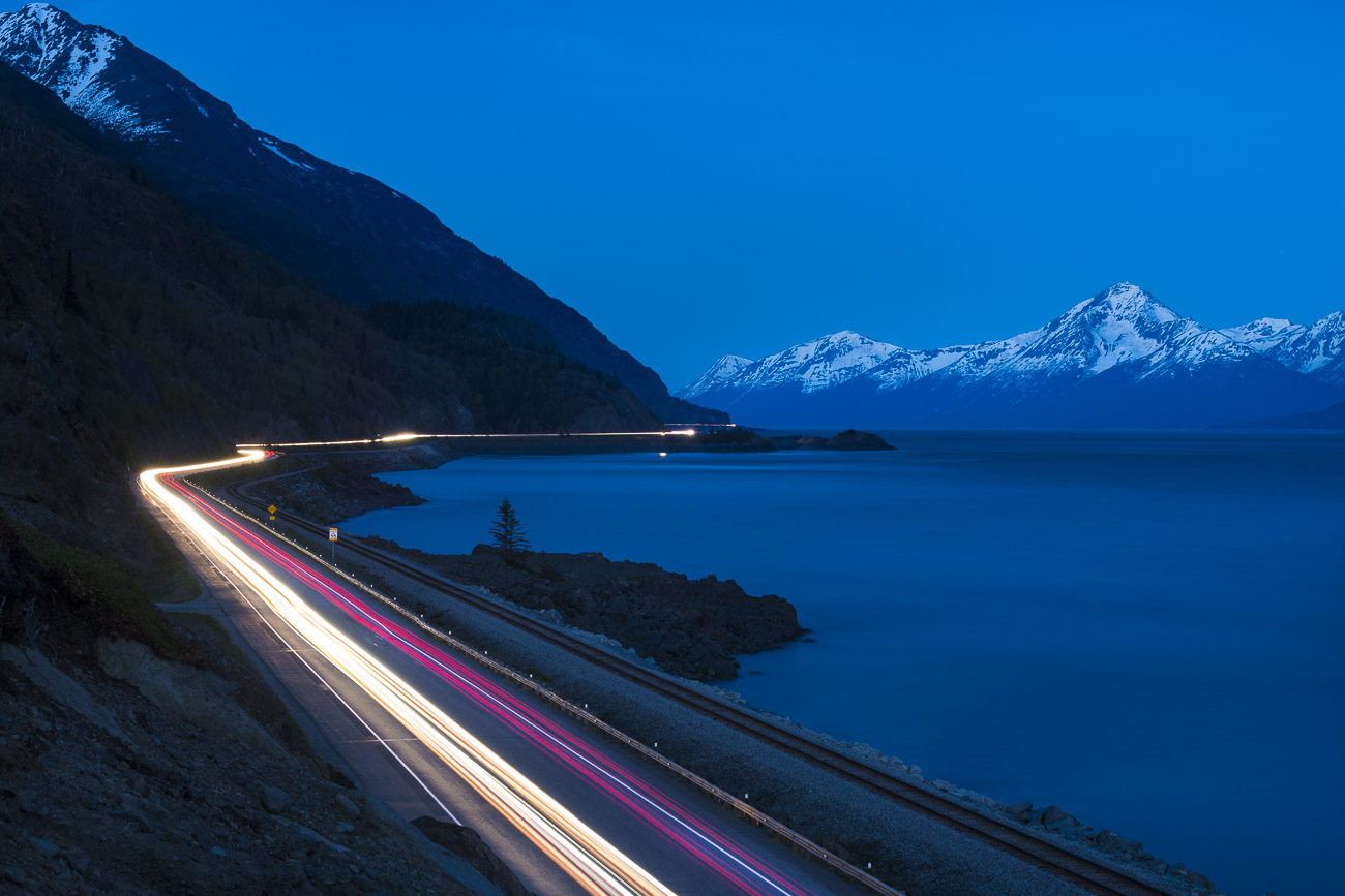 Streaks of headlights and taillights are caught using a long exposure at twilight, as traffic moves up and down the Seward Highway...