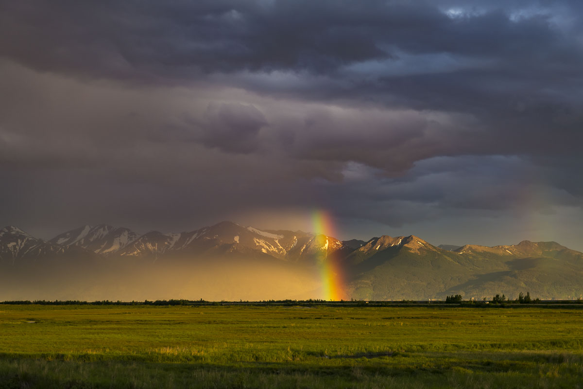 A bright rainbow pierces darkness of a summer thunderstorm at Potter Marsh in Anchorage.