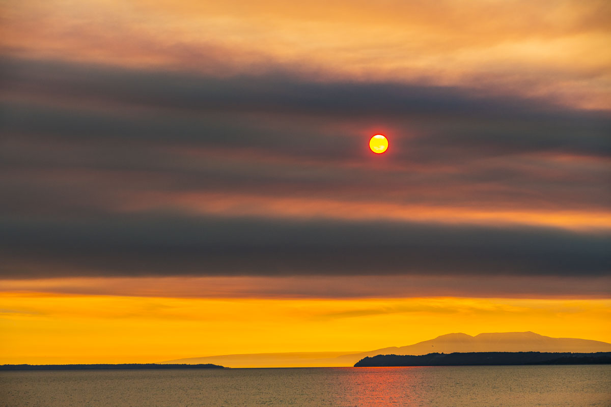 Dense fire smoke from the Swan Lake fire in the Kenai National Wildlife Refuge mutes the sun over Mt. Susitna and Cook Inlet.