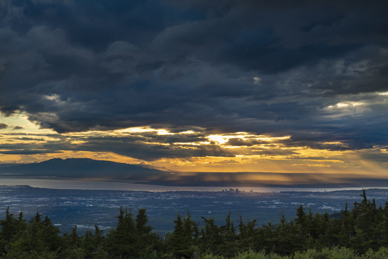 Several shafts of light break through the clouds during a summer storm over Anchorage.