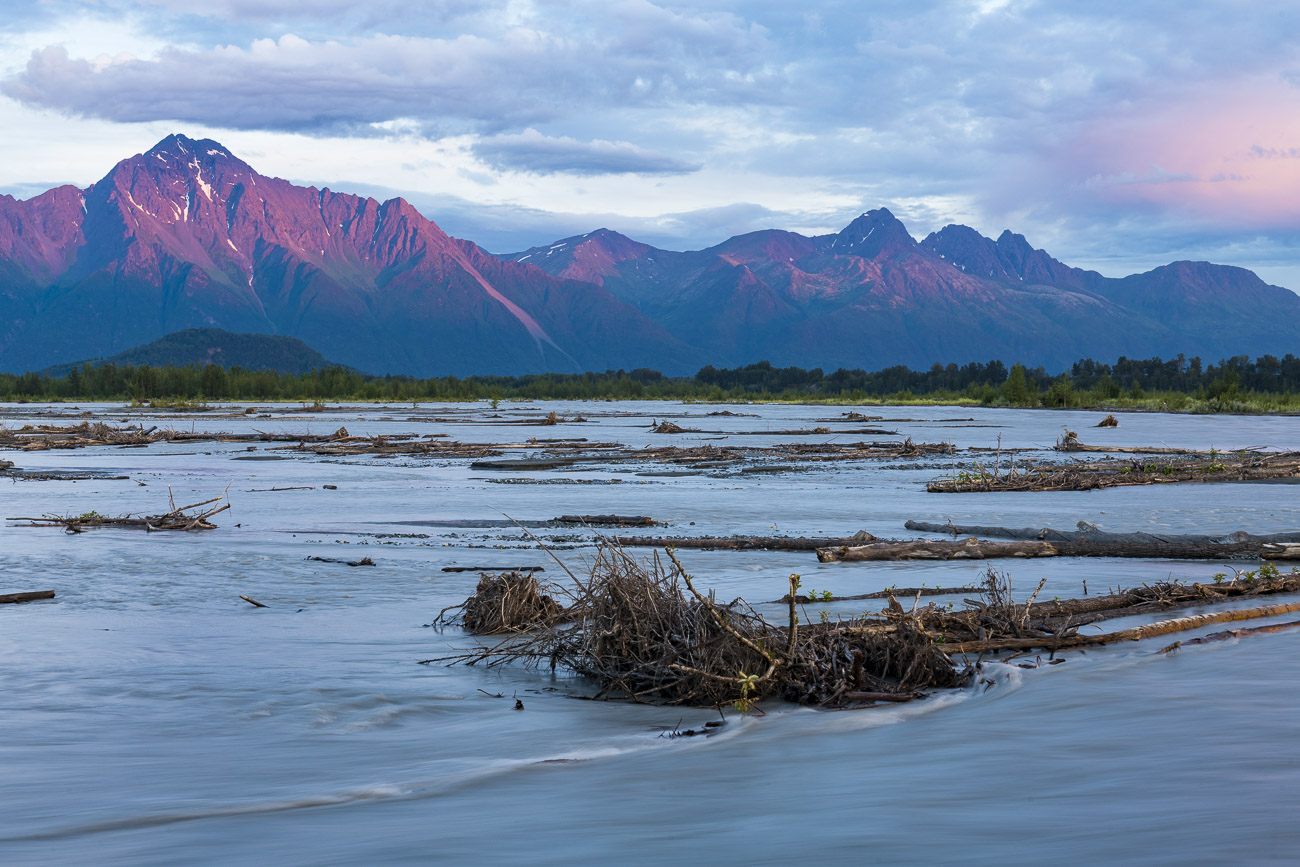 Apenglow creates a pink lighting of Pioneer Peak as the Matanuska River flows in the foreground.