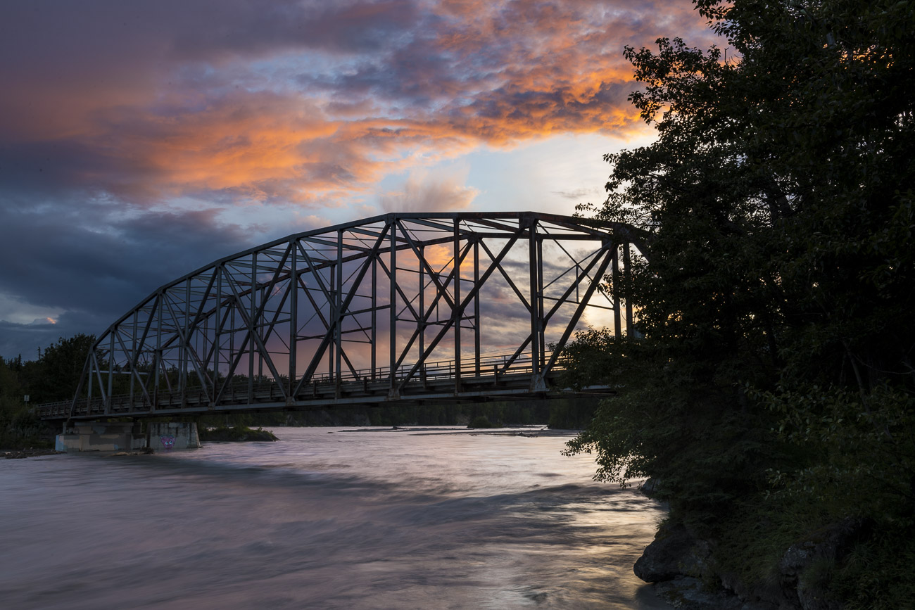 A bridge over the Matanuska River sillhouettes against the colors of sunset on a summer evening.