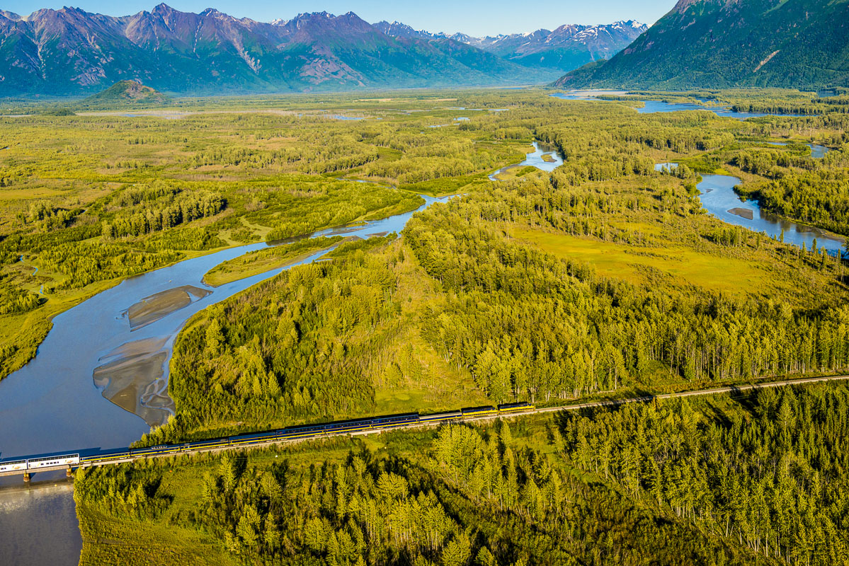 Aerial view of Alaska Railroad passenger train crossing one of the channels of the Knik River near Palmer, Alaska.