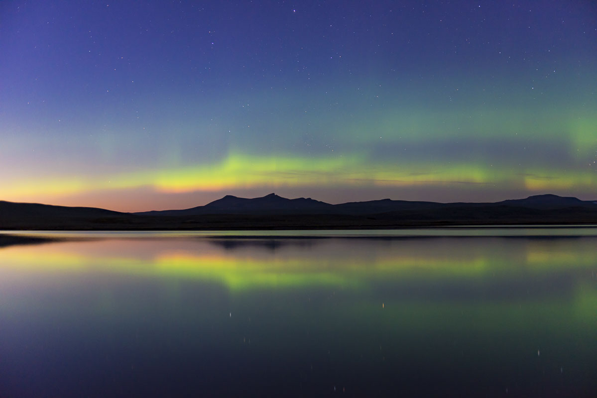 An aurora borealis display dances early in the evening and in the season in late August at Crosswinds Lake, Katmai National Preserve...