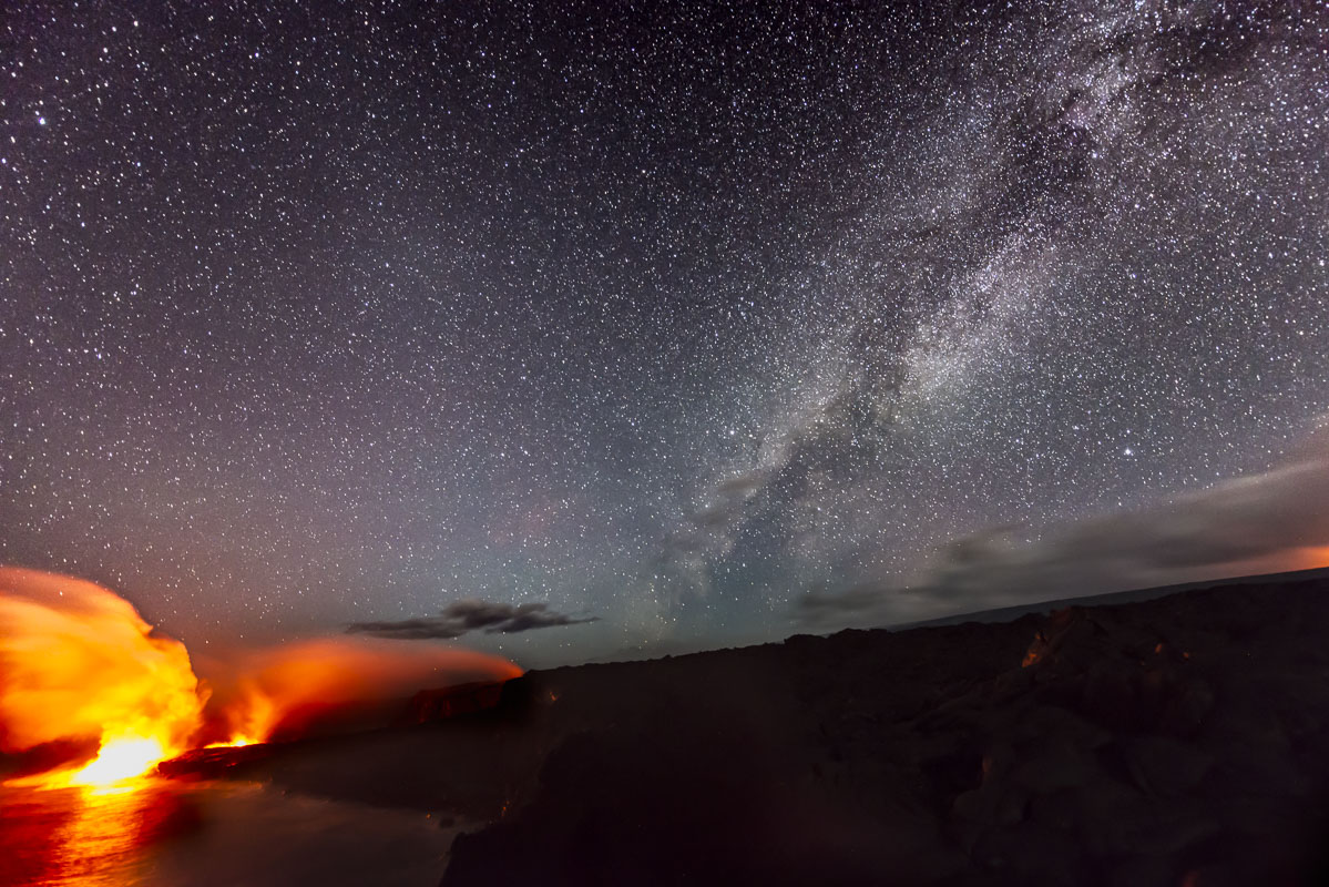The Milky Way floats in the night sky over lava flowing into the ocean, adding to the continual growth of the land at Hawaii...