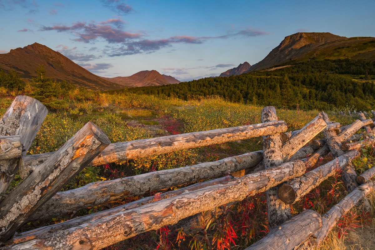 Wooden variation of a snow fence design lines the trail with O'Malley, Ptarmigan and Flattop in the background.