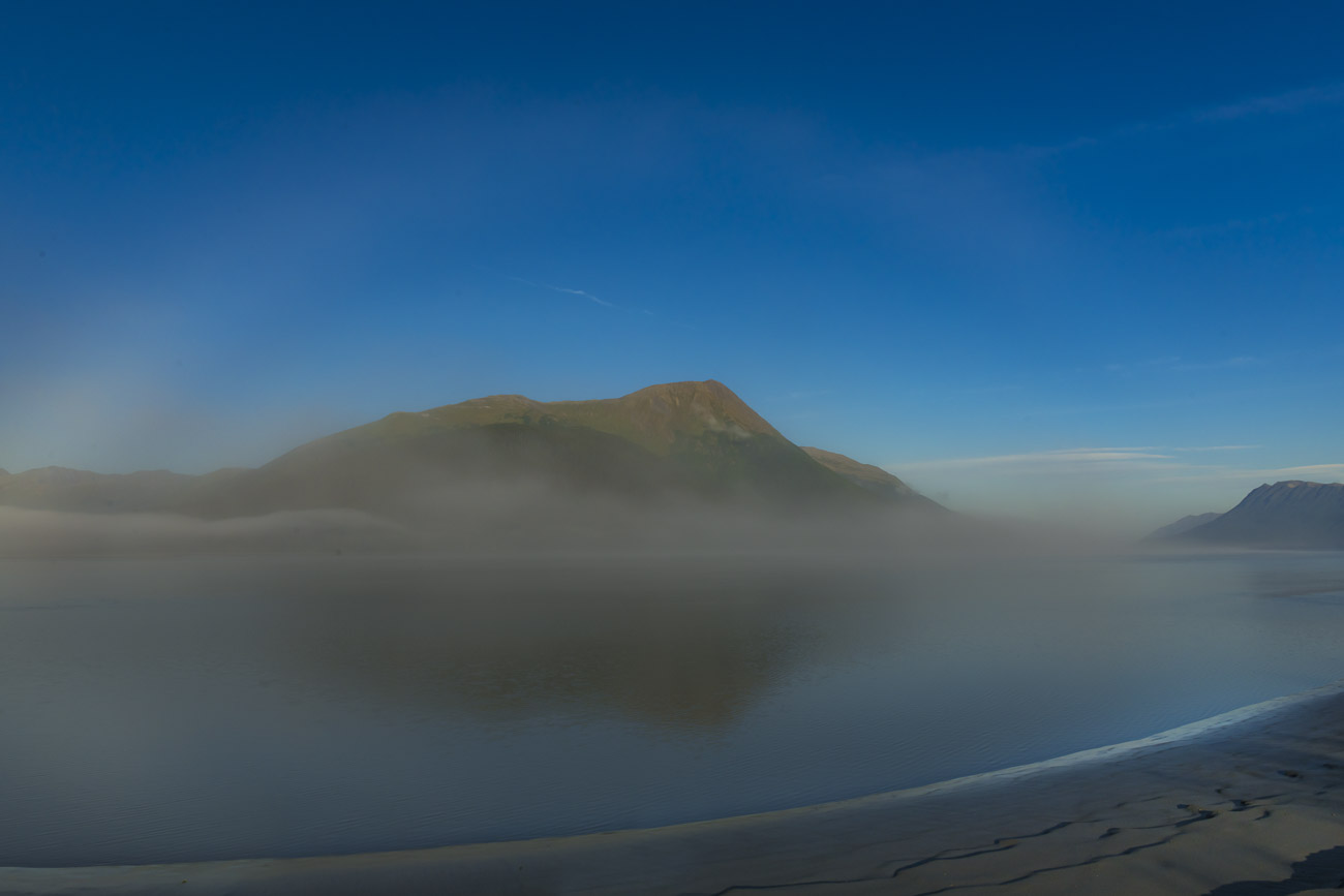 A fogbow, or white rainbow, appears on a calm morning in thin fog along the Turnagain Arm.