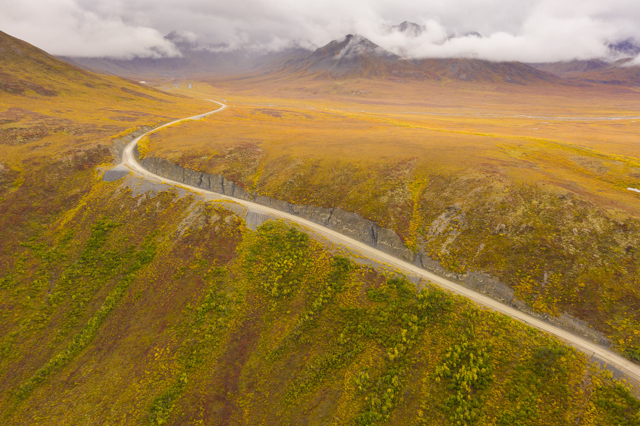 The Dalton Highway climbs up to the Chandalar Shelf as fall colors spread across the tundra.