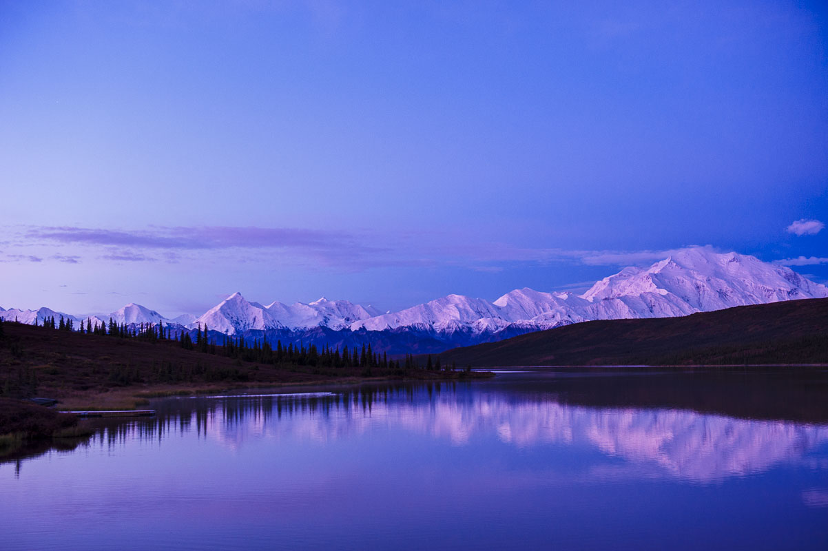 The calm waters of Wonder Lake provide a perfect reflection for Mt. Denali as the colors of dawn glow on its slopes in Denali...