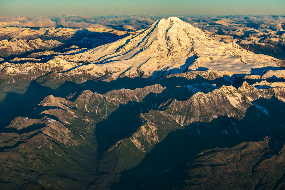 A snow-covered Mt. Redoubt rises above nearby ridges in the Aleutian Range in early light in September.