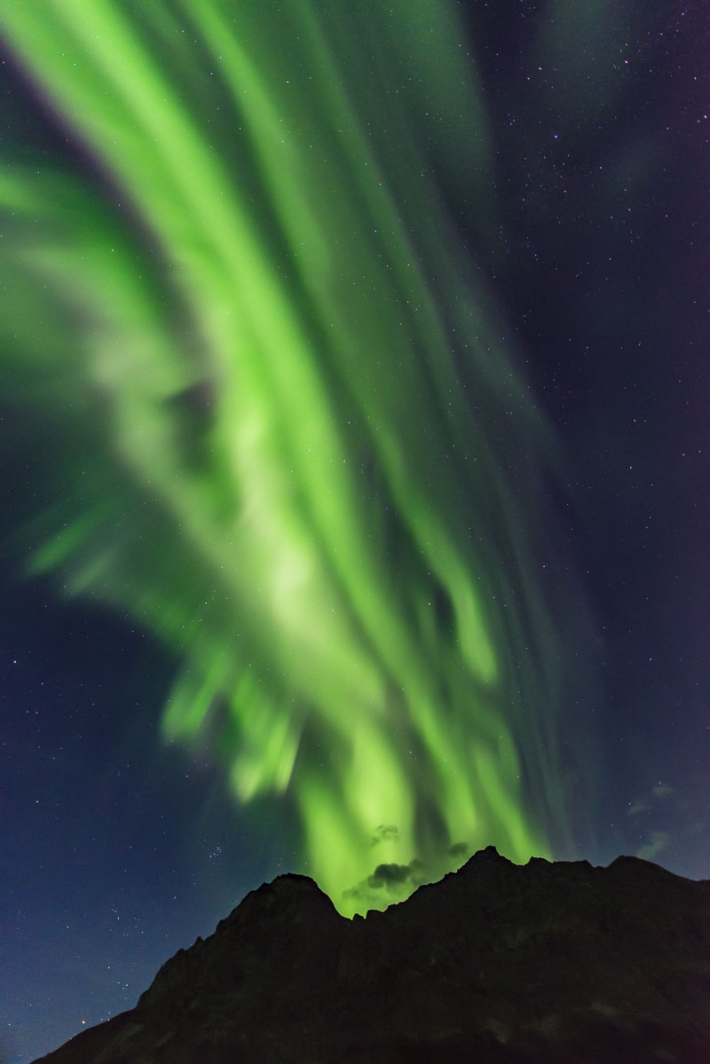 The aurora borealis seems to erupt from the summit of Mt. Sukakpak in the Brooks Range near the Middle Fork of the Koyukuk River...