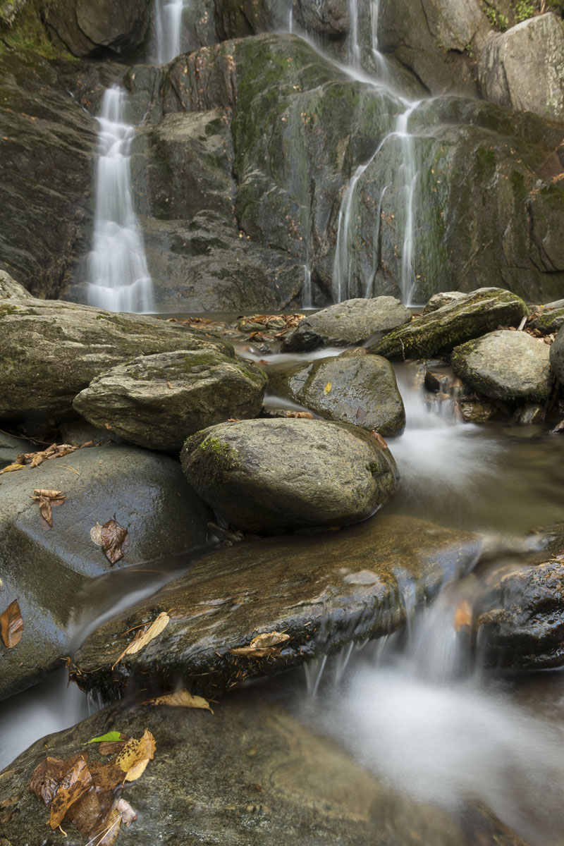 Various flows of a waterfall cascade down a series of rocks in the Granville Reservation in Vermont in early autumn.