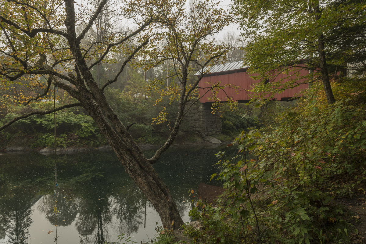 A light fog diffuses the air surrounding a covered bridge and river in Vermont.