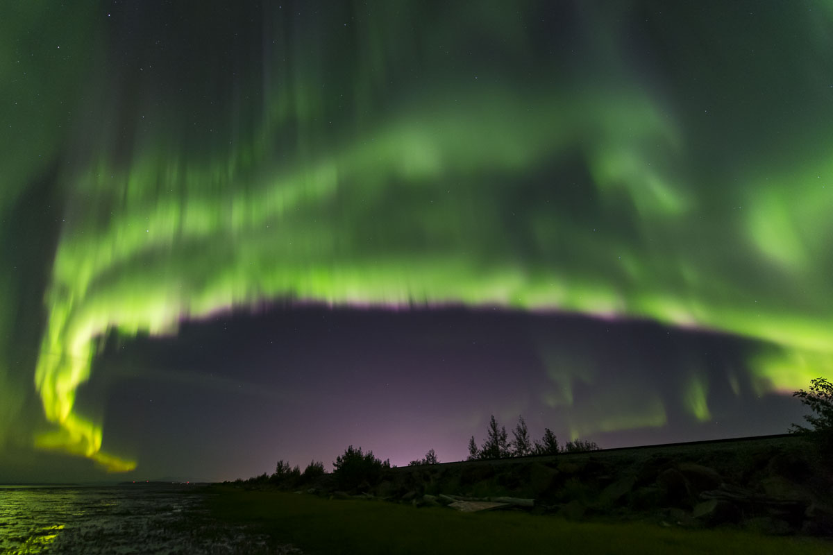 Aurora borealis over coastal Anchorage in early autumn. The glow of the city can bee seen in the middle bottom, showing that...