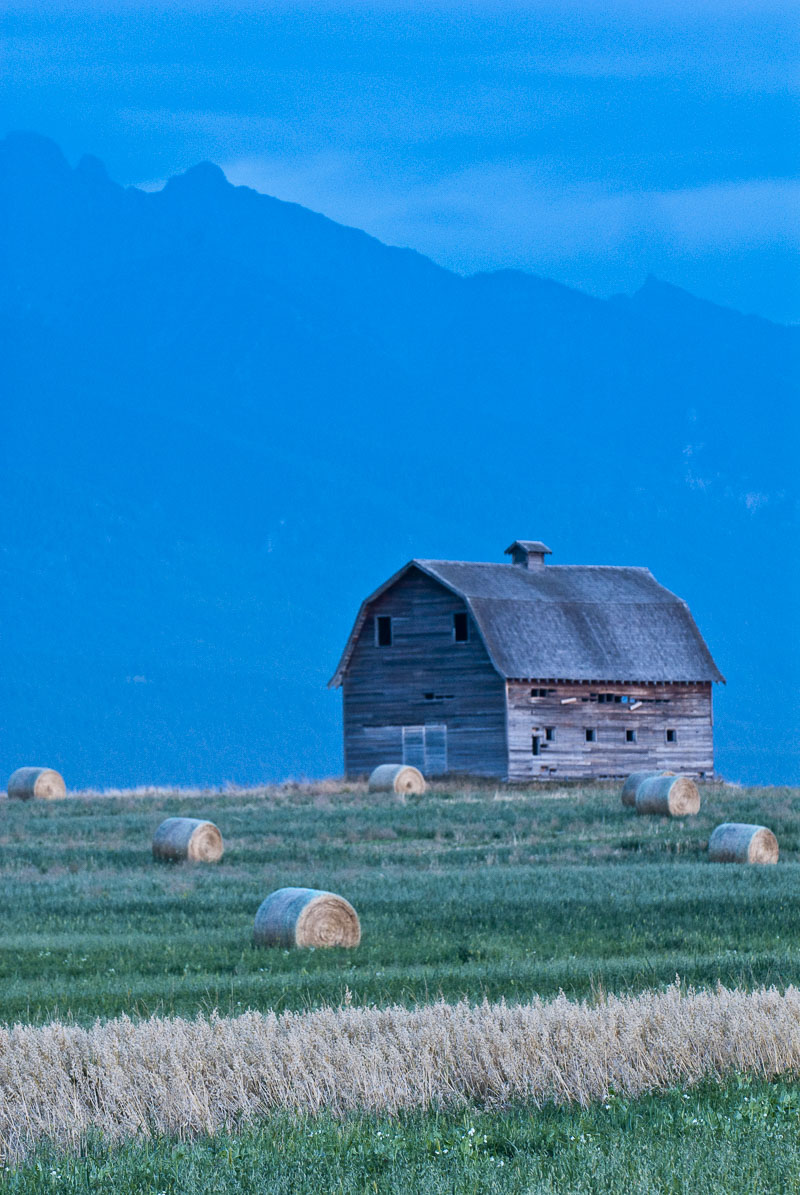 Twilight is falling on the Flathead Valley, Montana, when I find this old barn and some rolled hay in a field.