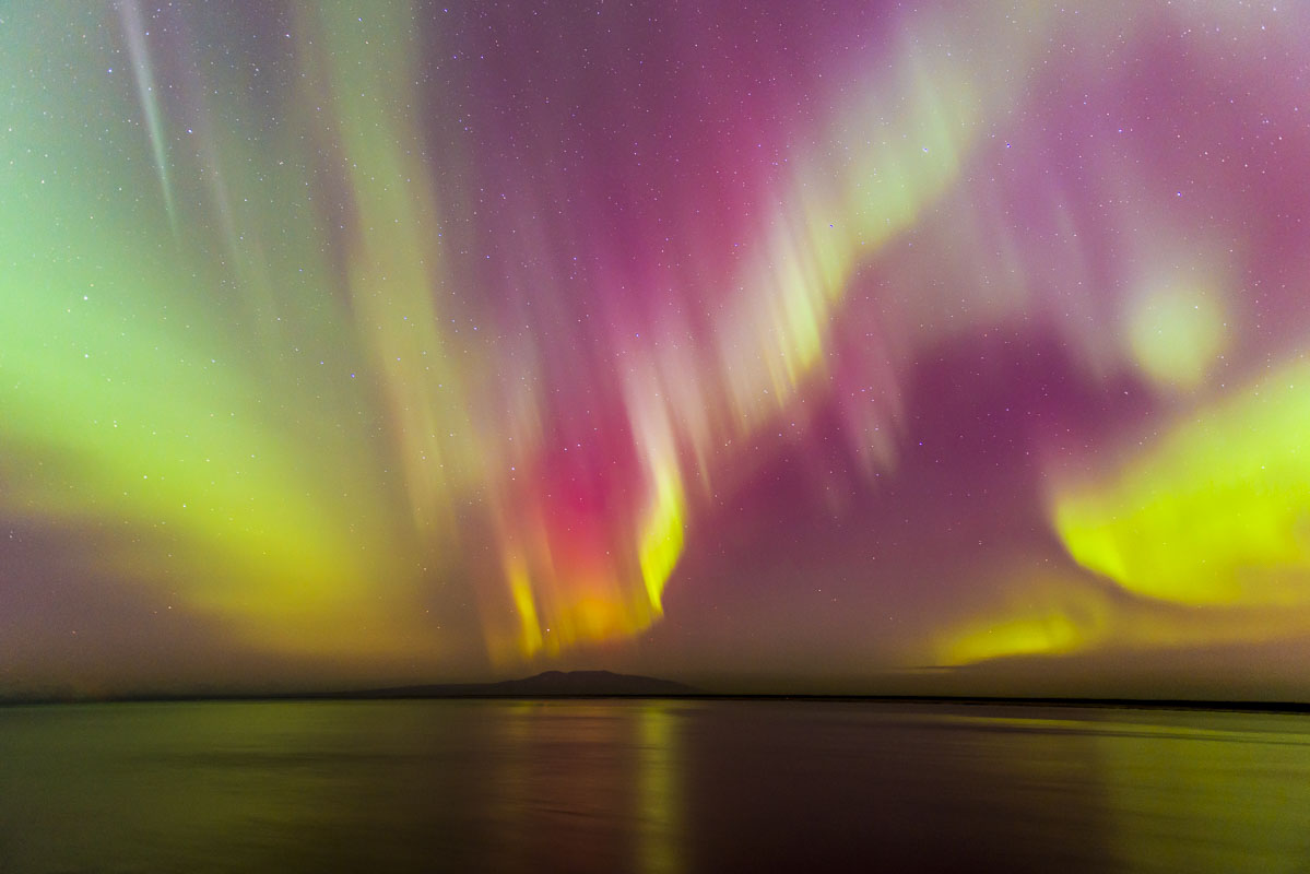 """Aurora borealis display over Cook Inlet and Mt. Susitna (aka """"Sleeping Lady"""") as viewed from Point Woronzof in Anchorage."""