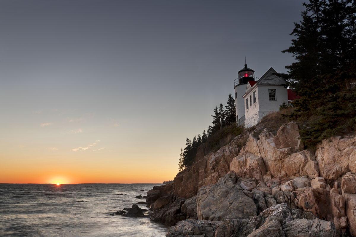 The sun dips below the horizon in autumn at the Bass Harbor Head Lighthouse, Acadia National Park, Maine.