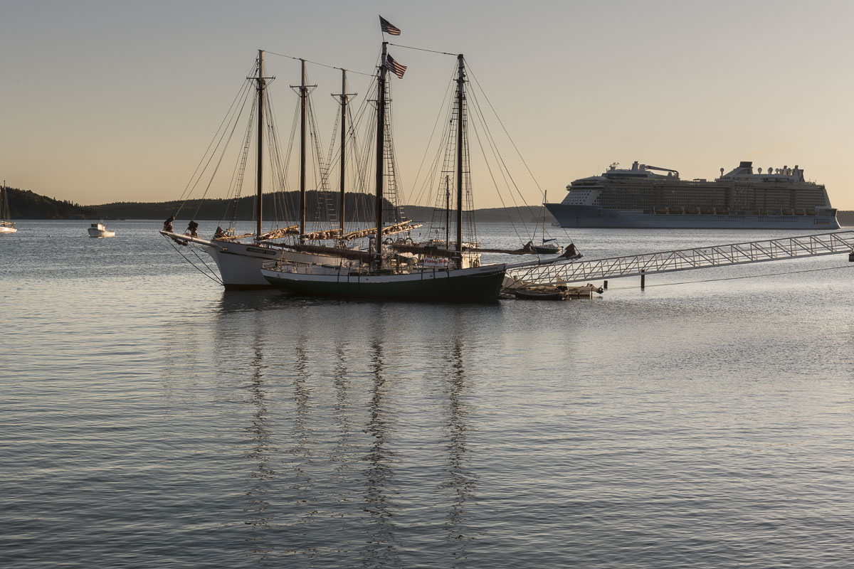 Traditional sailing vessels sit in anchor in contrast to the massive Anthem of the Seas, a 4905-passenger Royal Carribbean cruise...