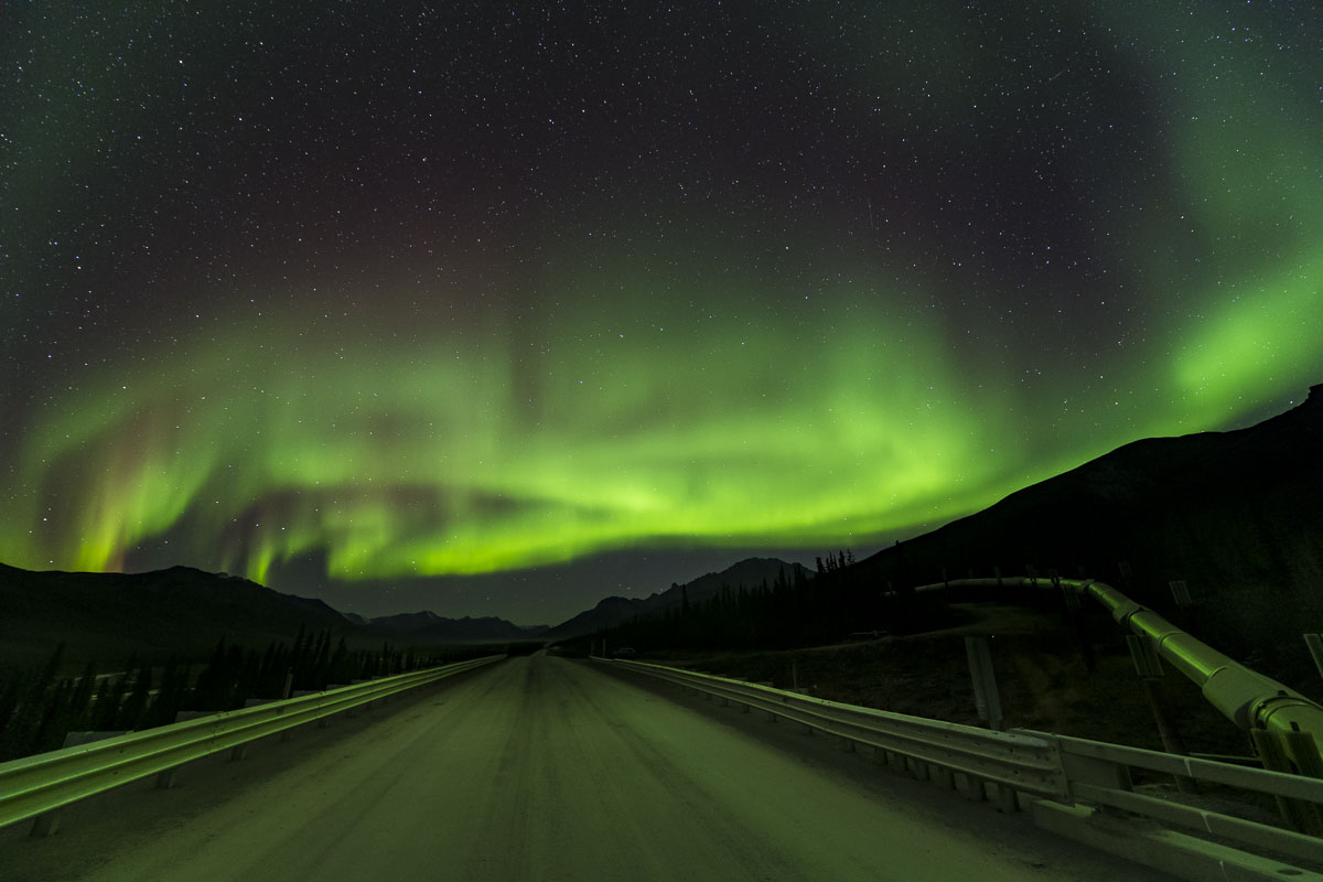 The aurora borealis dances in the northern sky over the Dalton Highway and Trans-Alaska Pipeline in the Brooks Range of Arctic...