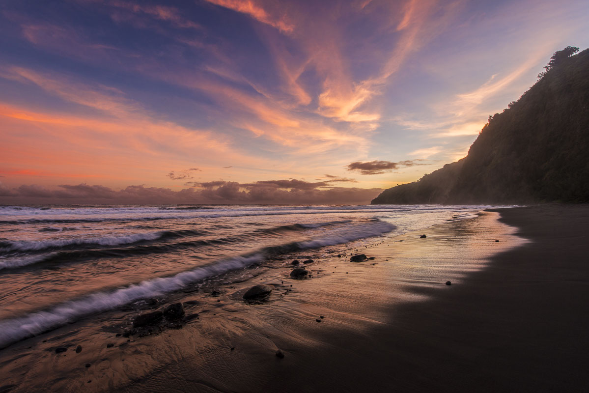 Whispy clouds and surf catch hints of color at morning in Waipao Valley, Hawaii.