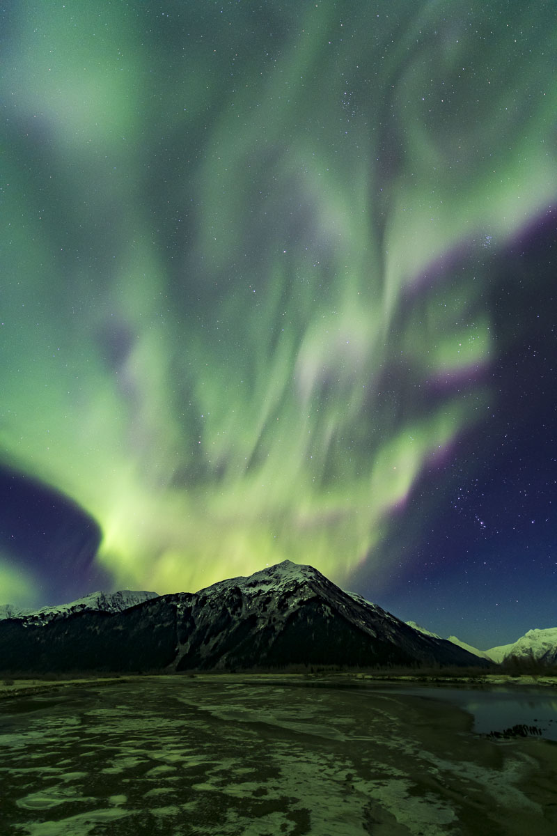 The aurora borealis seems to erupt over a mountain in Chugach National Forest during an early winter display.