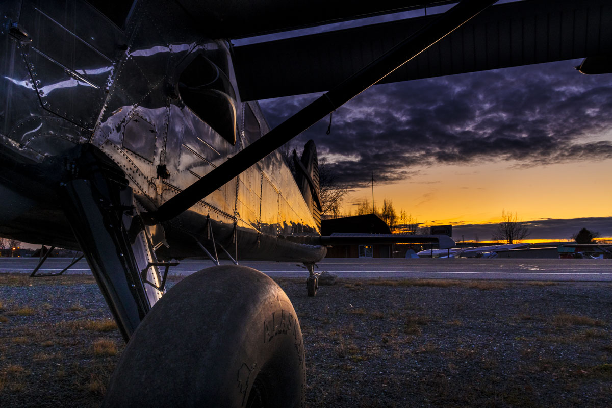 The colors of dusk reflect on the side of a bare metal small plane at the Lake Hood Seaplane Base in Anchorage.