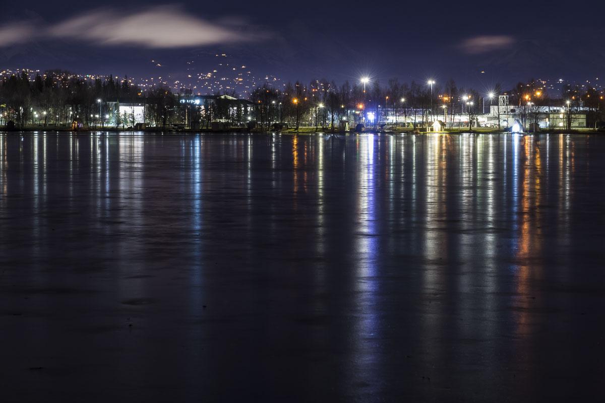 The frozen waters of Lake Spenard reflect shoreside lights in early winter.