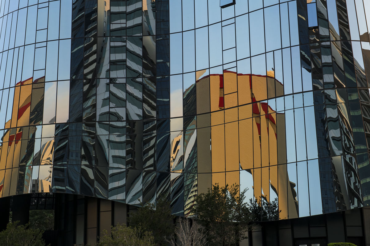 Various buildings distort and reflect in a glassy tower in downtown Brisbane, Australia.
