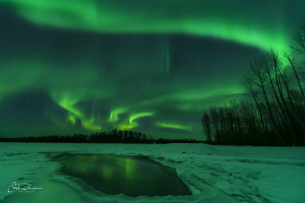 The aurora borealis swirls in the sky over the confluence of the Chulitna, Talkeetna and Susitna Rivers near Talkeetna, Alaska...