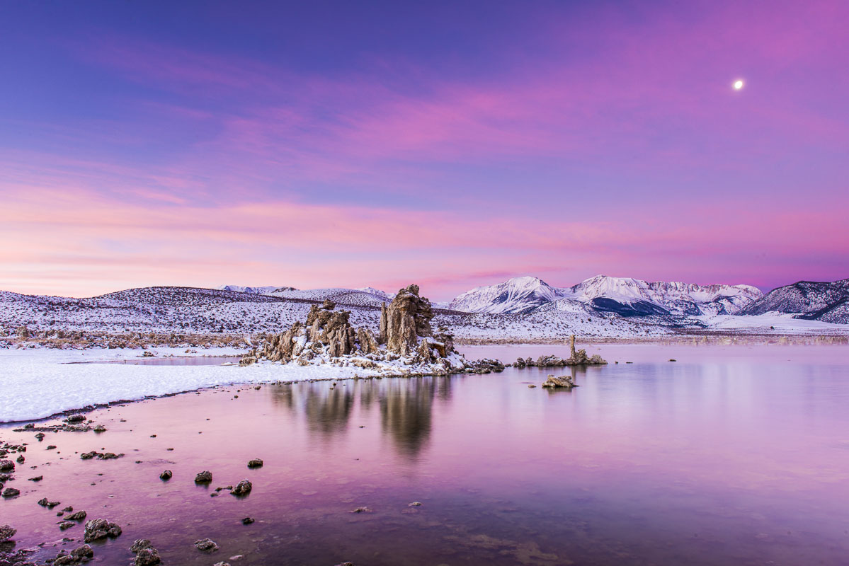 The moon hangs high in the sky as the colors of sunrise start to light up the landscape at Mono Lake, California.