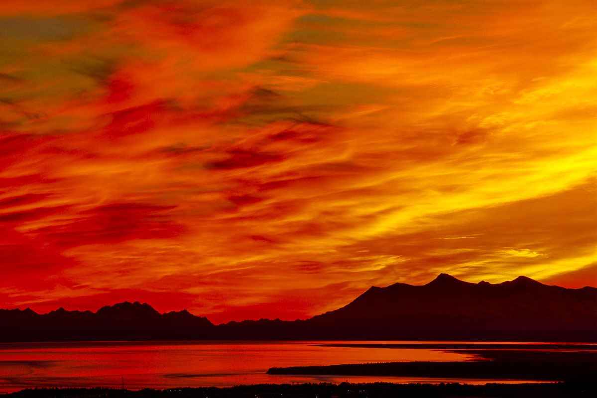 A fiery sunset lights up the sky above the Tordrillo Mountains and Alaska Range in this view from Arctic Valley in Anchorage....
