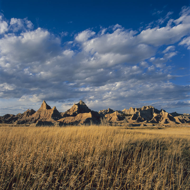 Evening light shines on a series of formations in the North Unit of Badlands National Park, South Dakota. When viewed from a...