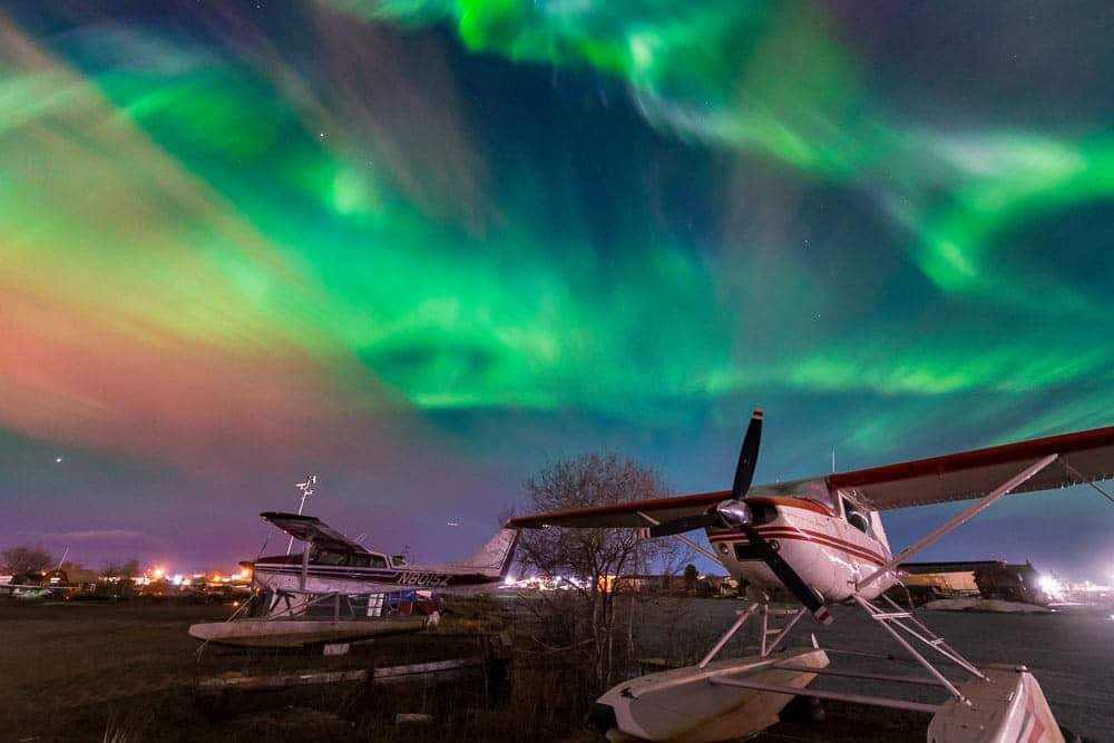 The aurora borealis sours high in the sky with an active display while float planes sit over winter at the Look Hood Seaplane...