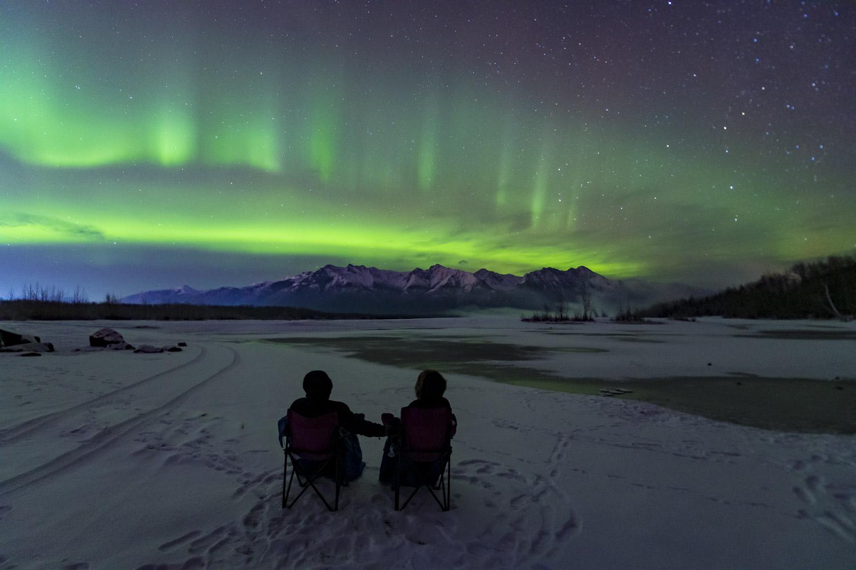 A couple enjoys a relaxing view of the aurora borealis during a tour.