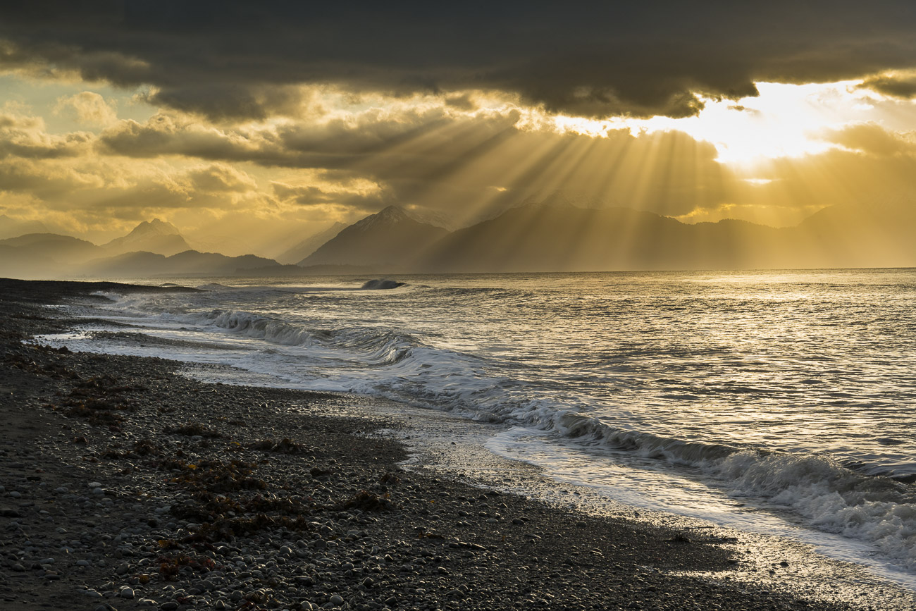 A fan of morning sun rays sprays across Kachemak Bay as a light surf pounds the sand and rock of Bishop's Beach in Homer, Alaska...