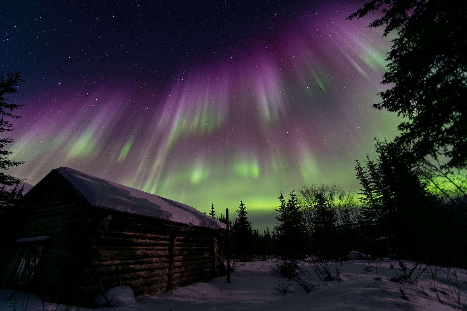 The aurora borealis fills the sky over the Kalhabuk Memorial Chapel in Wiseman, Alaska.